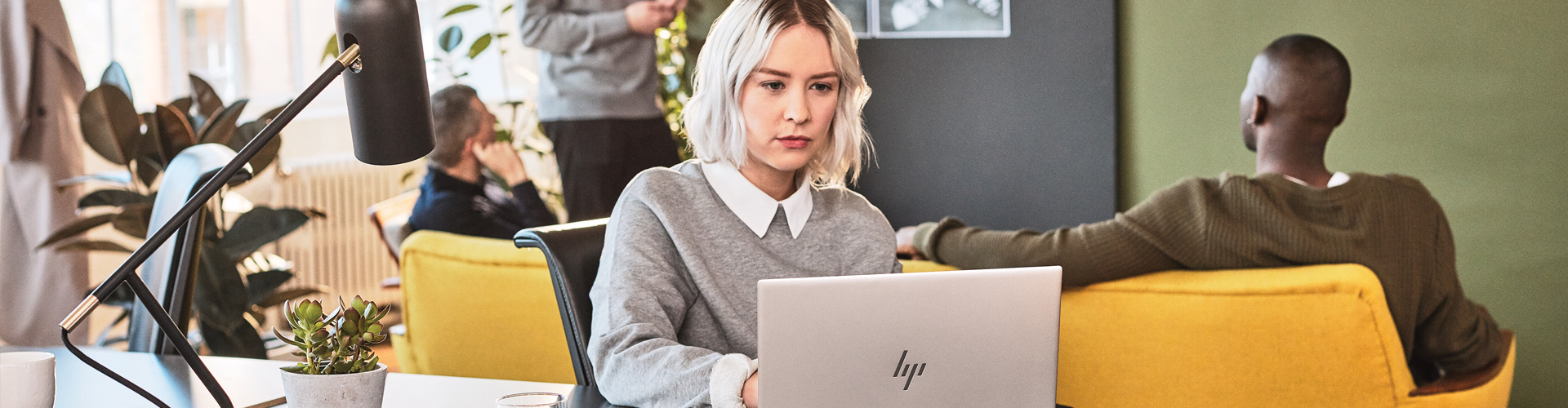 A woman on a laptop in an office setting