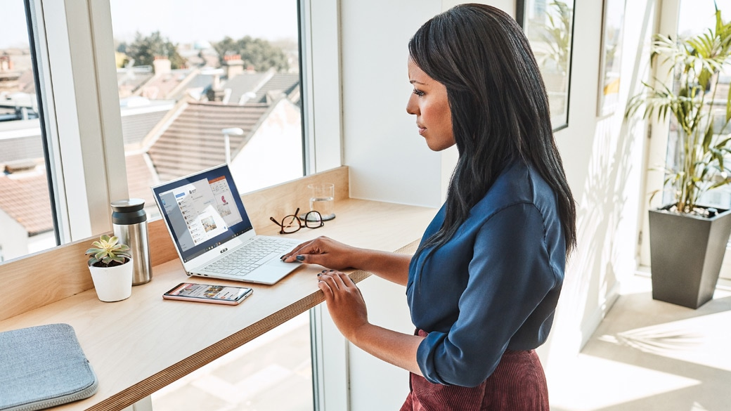Woman standing at a desk with her phone and a Windows 10 device.
