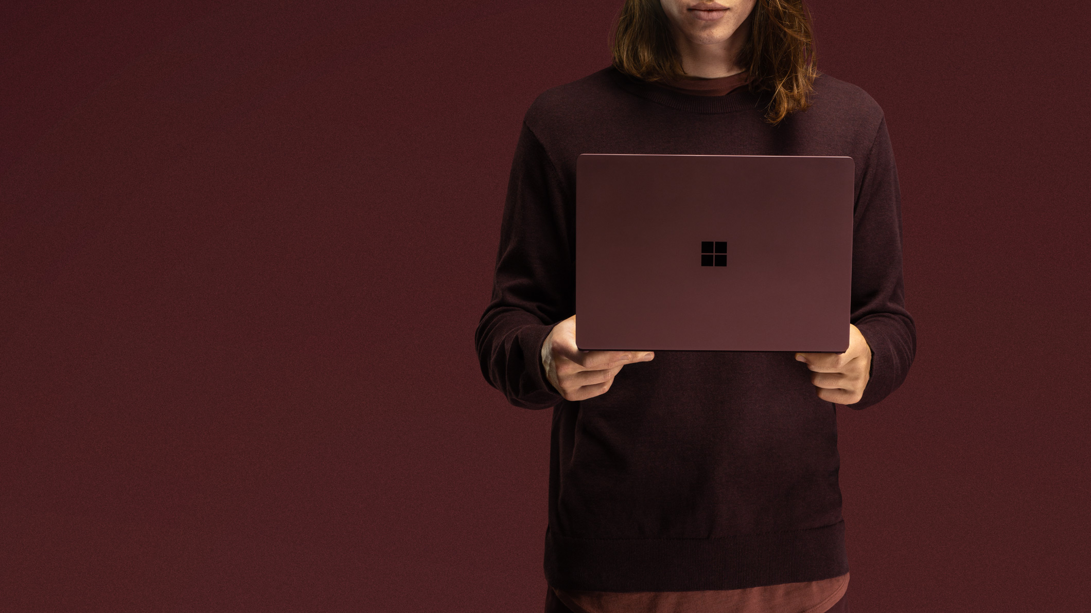 En person i en bordeauxrød sweater står op og holder en åben Surface Laptop 2 i bordeauxrød