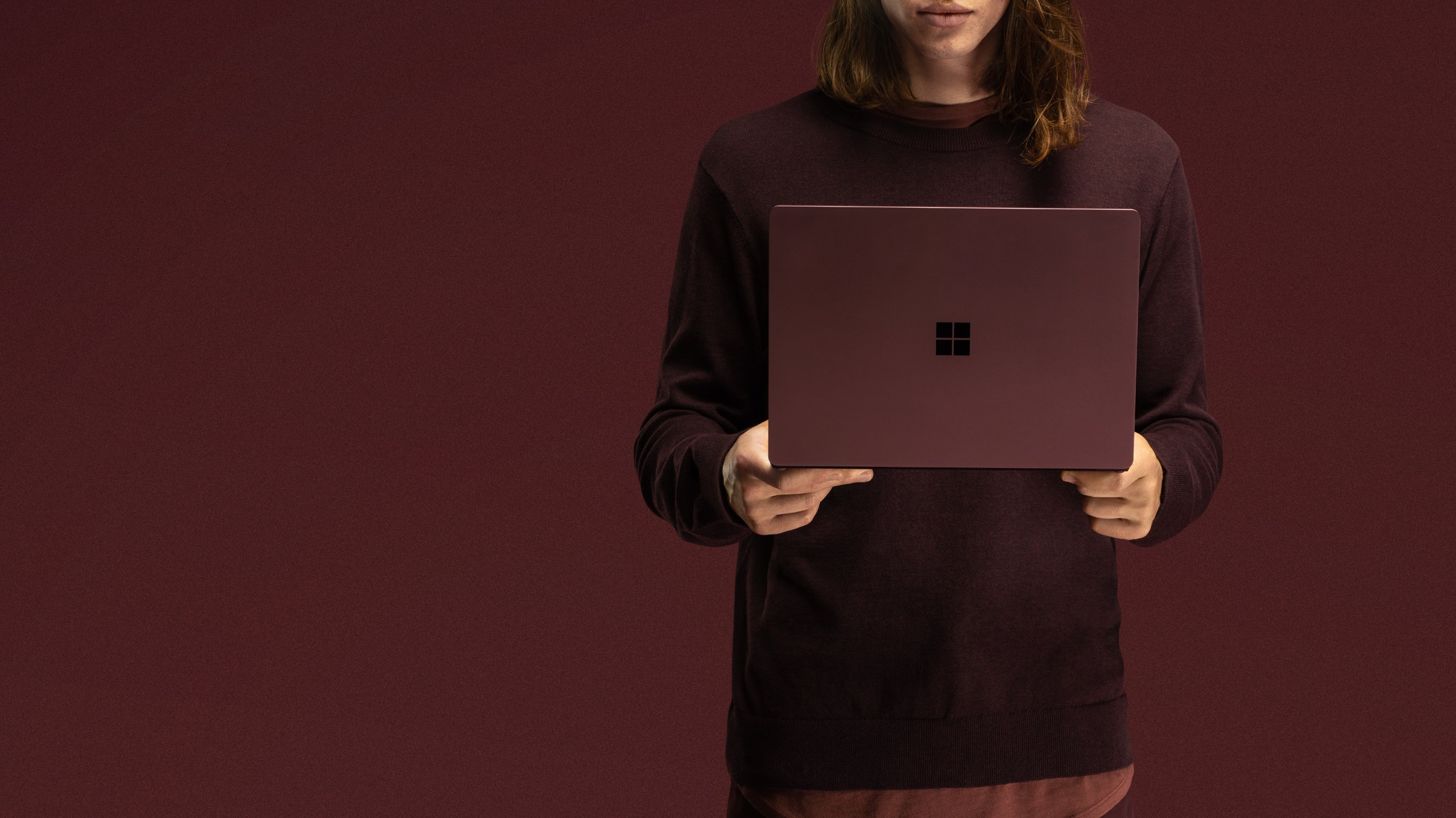 A person in a burgundy sweater stands holding an open Surface Laptop 2 in Burgundy