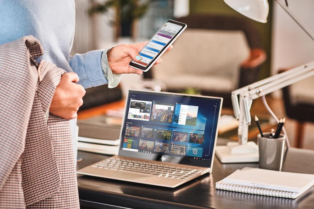 Femme regardant son téléphone avec son ordinateur en arrière-plan.