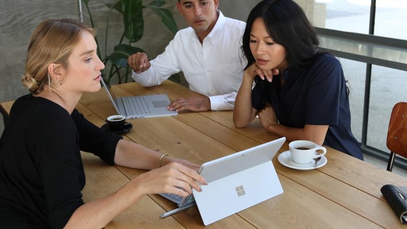 Tre kolleger sitter ved et kontorbord og ser på en Surface Pro 6-skjerm.