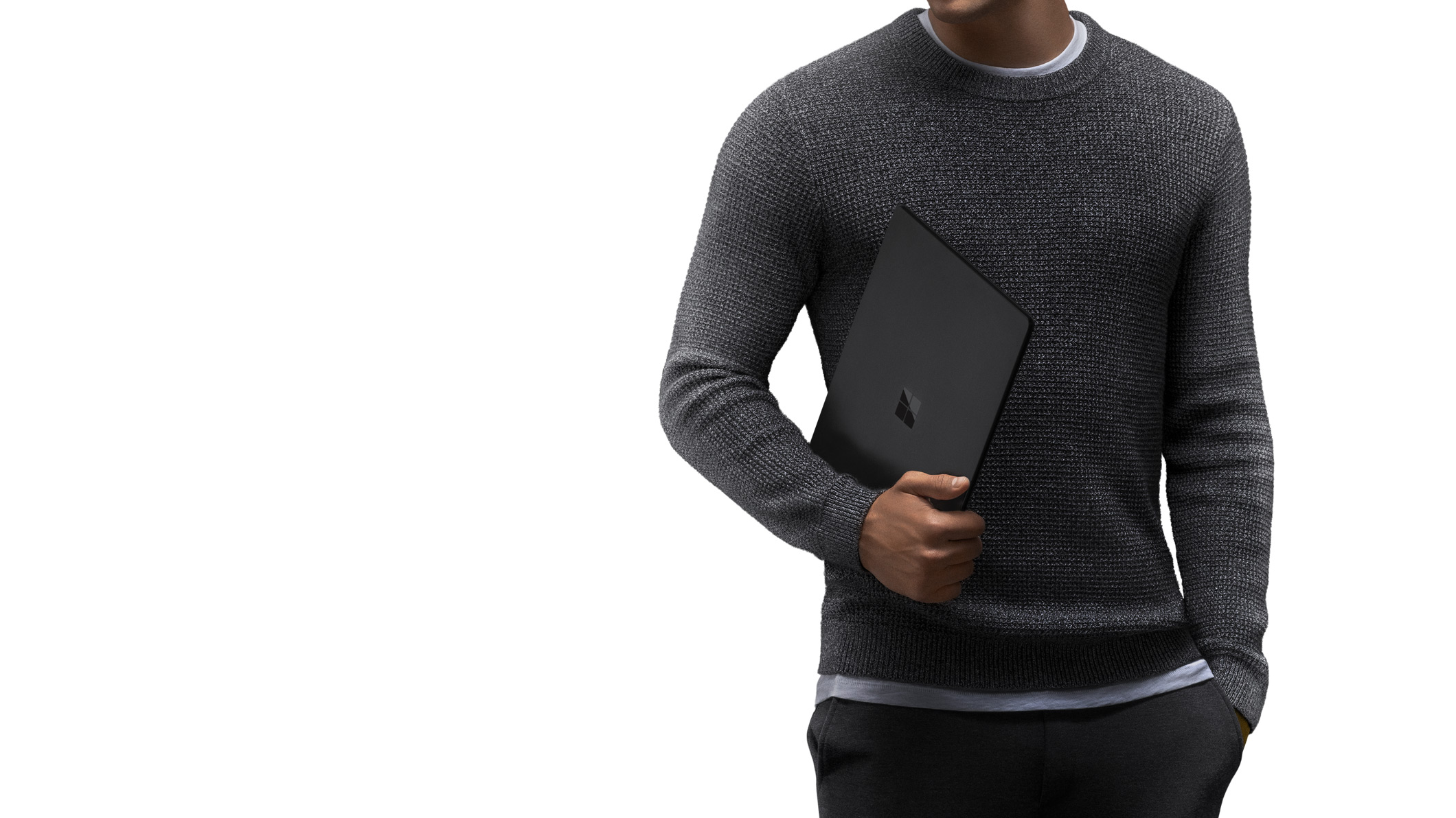 En mand i en grå sweater bærer Surface Laptop 2 i sort i sin arm