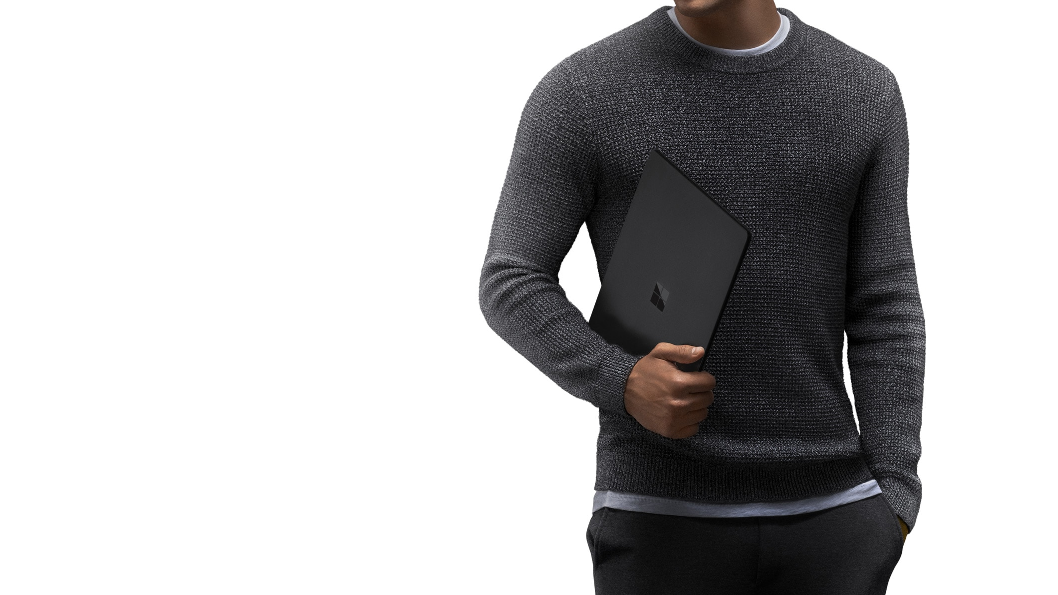 A man in a grey sweater carries Surface Laptop 2 in Black in the crook of his arm