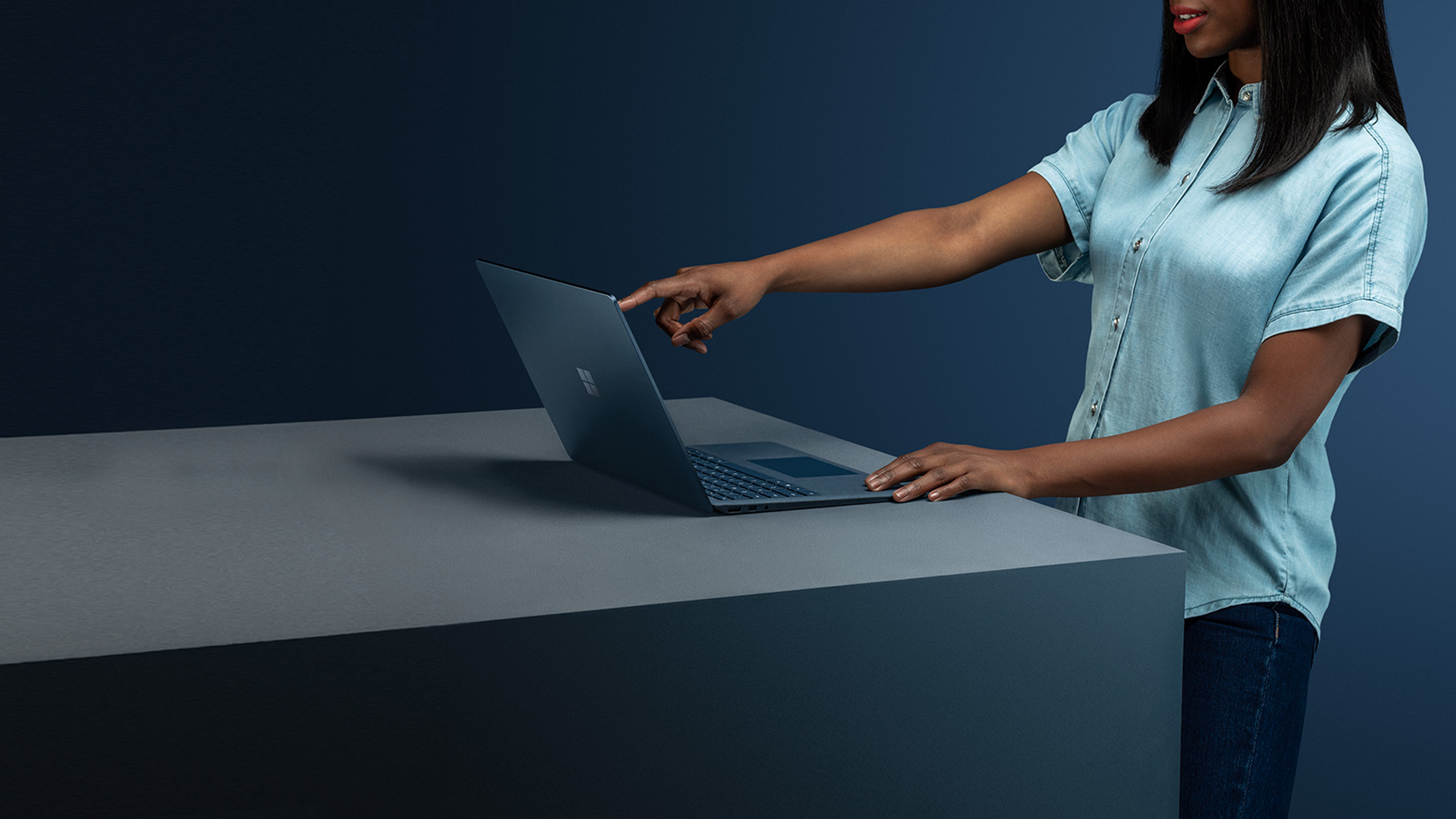 A woman in blue shirt touches the screen of a Surface Laptop 2 in Cobalt