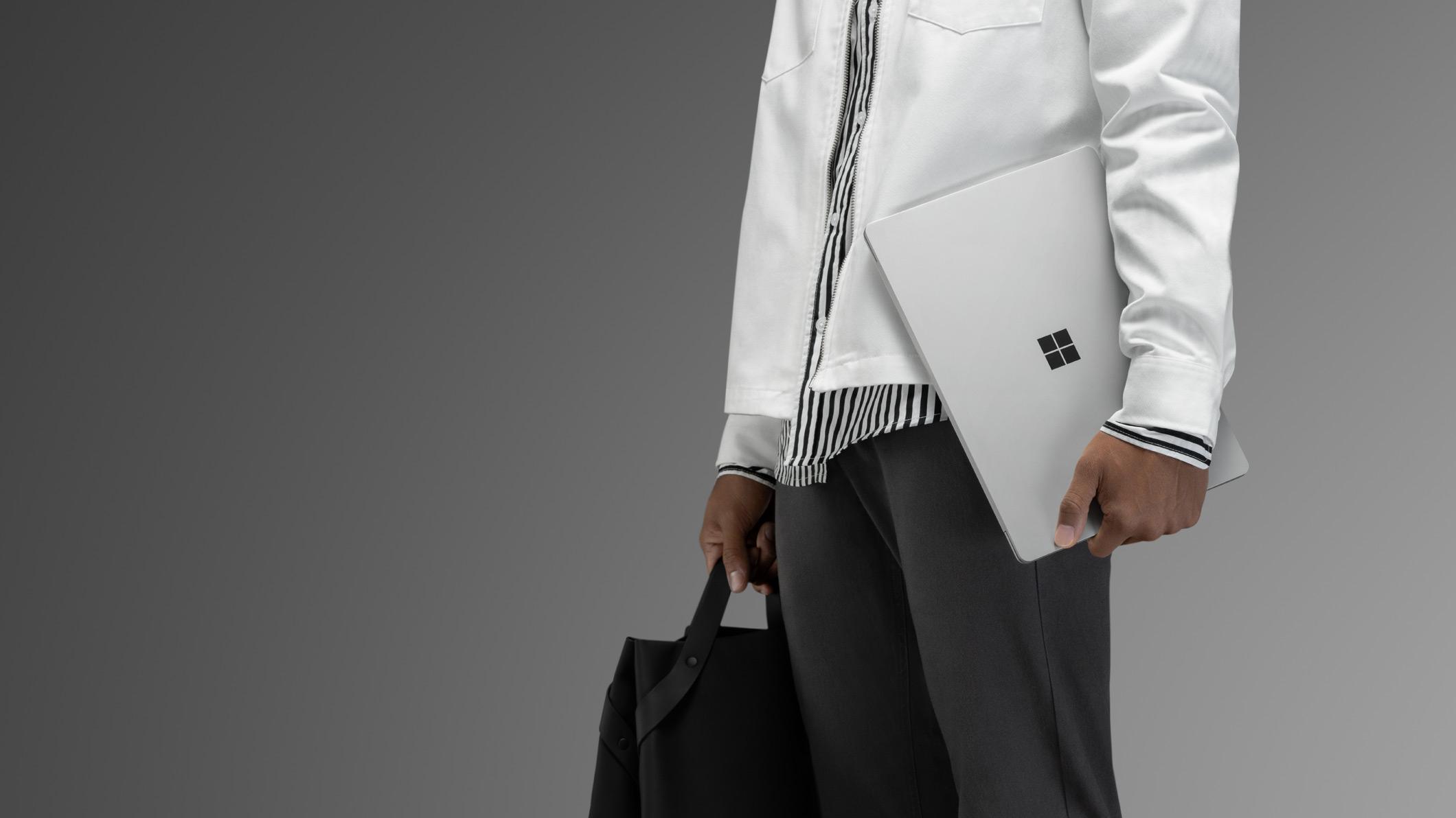 Un homme en veste blanche porte un SurfaceLaptop2 platine à côté de lui