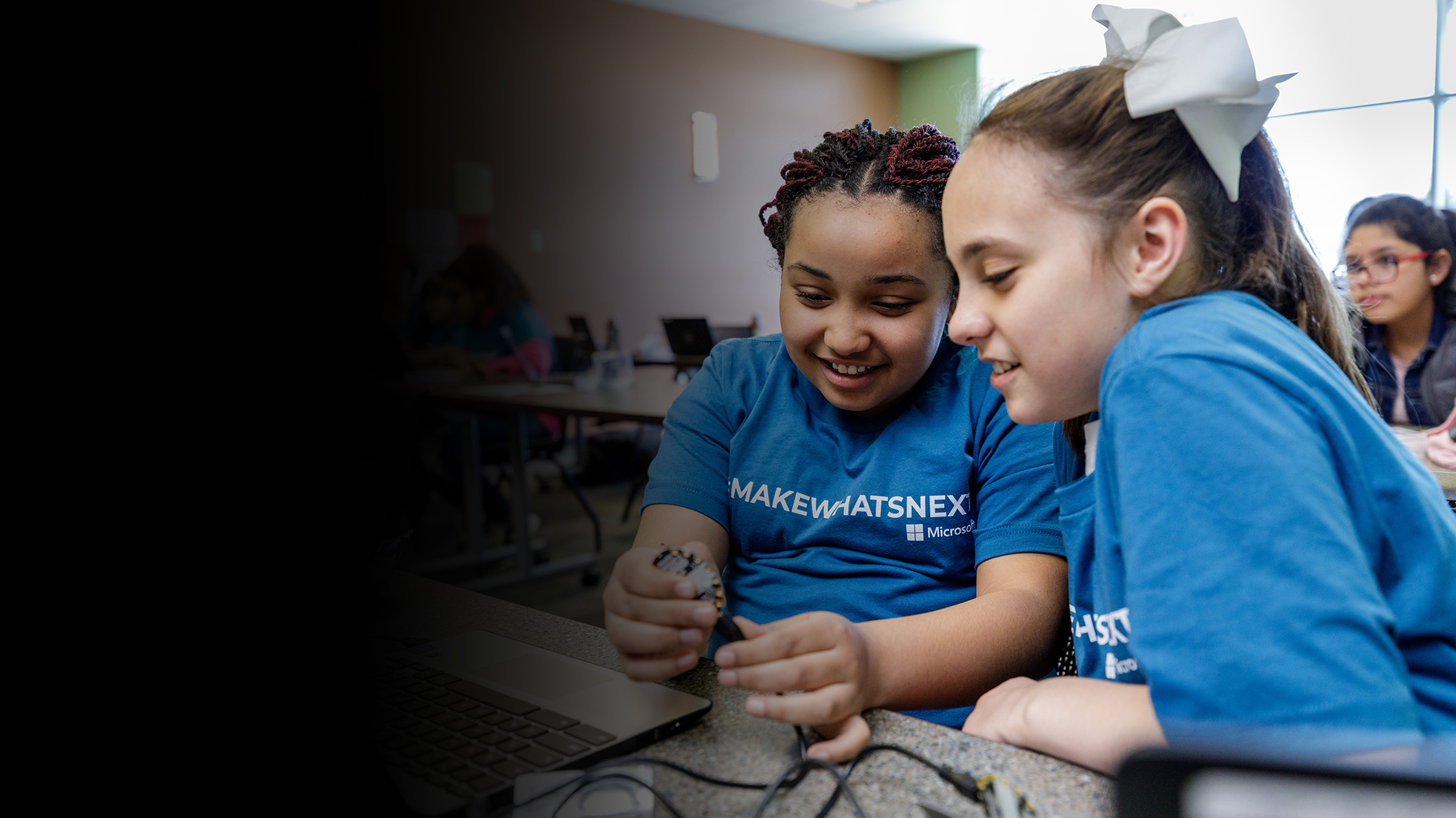 Two young girls work on a project with a computer chip.