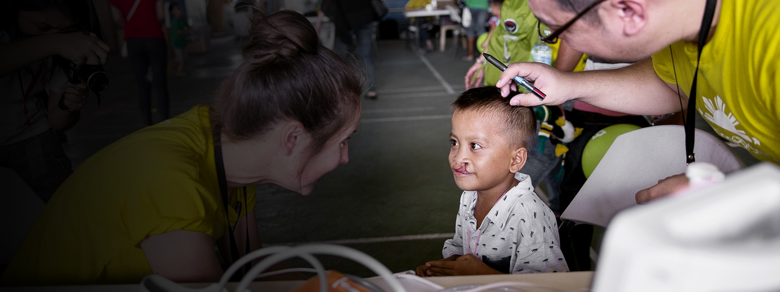 A woman talks to a young boy who has a disfigured lip.