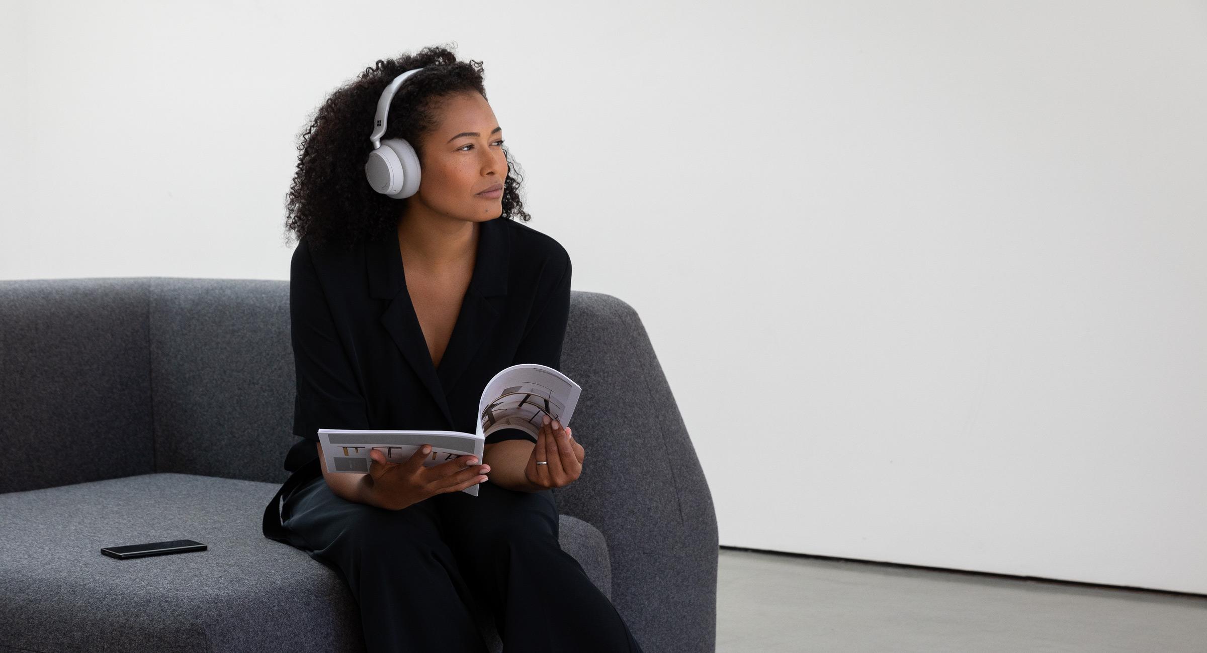 女人坐在长沙发上聆听 Surface Headphones