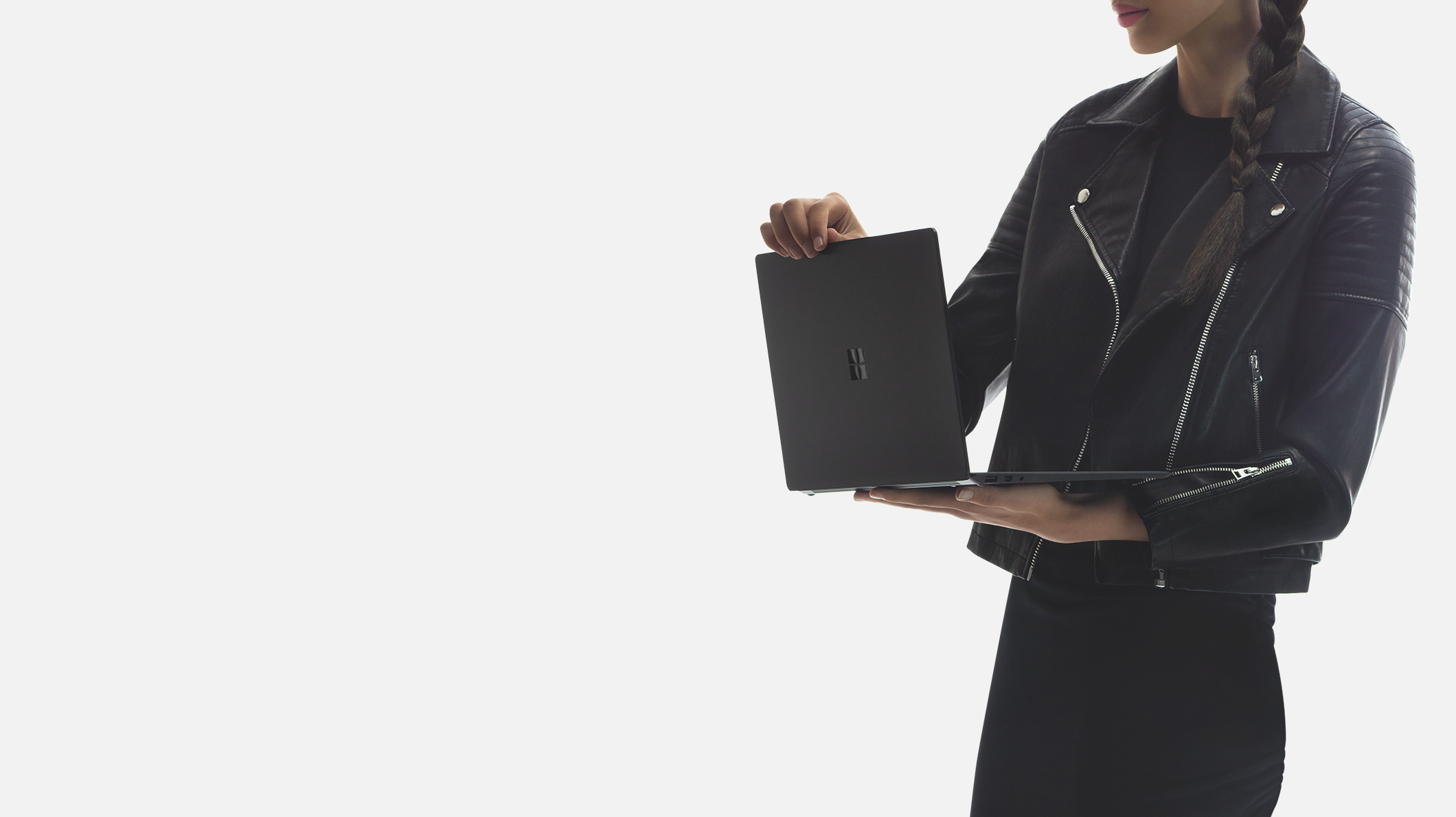 A woman holds a Surface Laptop 2 Store