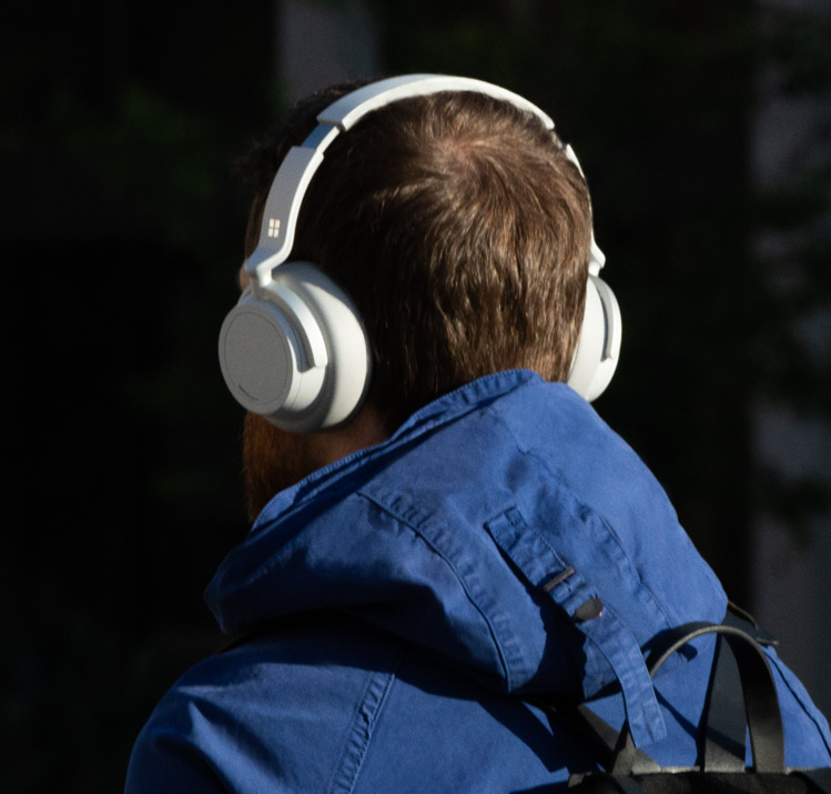 身穿蓝色夹克的男人头戴 Surface Headphones