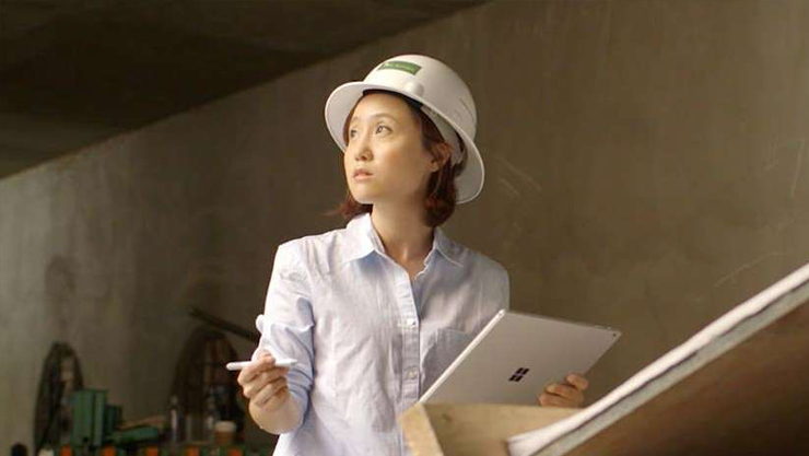 Architect Flora Lee wearing hard hat and holding Surface device