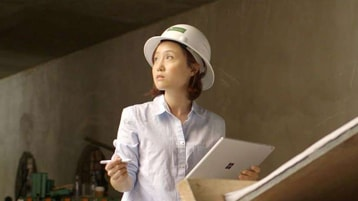 Architect Flora Lee wearing a hard hat and holding a Surface device