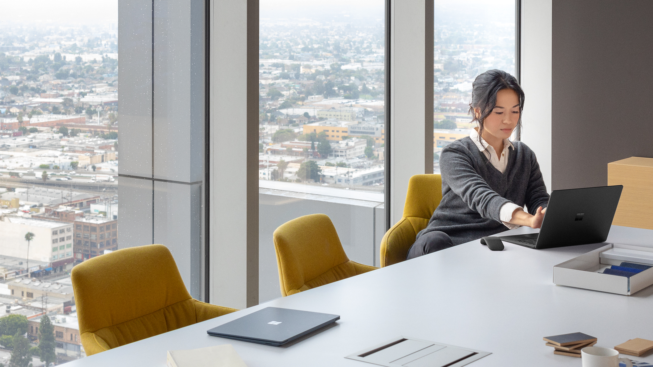 A woman works on a laptop in a conference room.