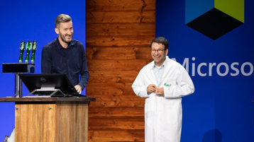 Jochen Förster and Judson Althoff in lab coat talking on stage at Microsoft Envision