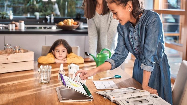 Мама помогает дочерям делать домашнее задание на компьютере с Windows 10.