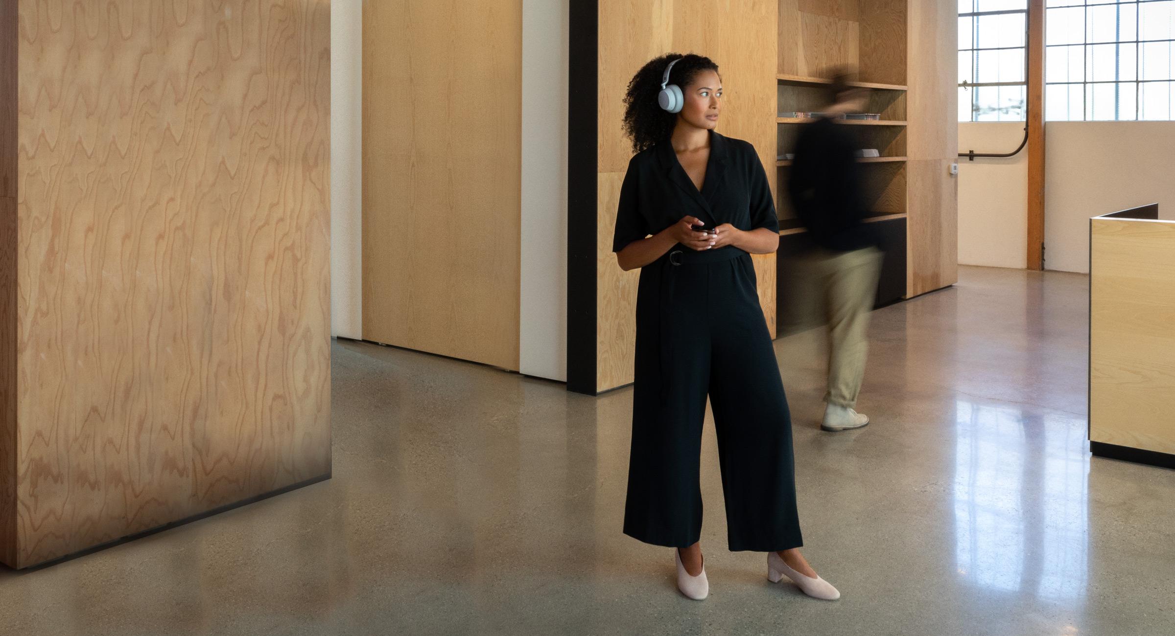 女人头戴 Surface Headphones 站立着