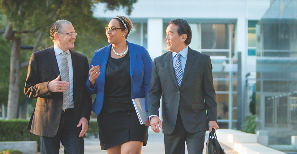Photograph of a diverse group of businesspeople talking while walking across a courtyard between two modern buildings