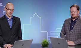 Still image from video with two people standing at a counter with their laptops