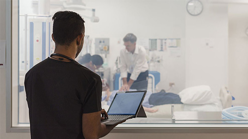 A man holds a laptop while watching two people care for a patient.