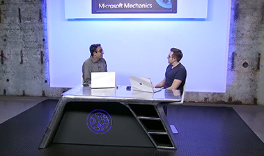 Still image from Microsoft Mechanics video with two people talking while seated at a desk with laptops