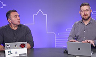 Still image from video of two people seated at a table, one person has a Surface Book and is addressing the camera, the other person has a Surface Pro and is looking at the person talking.