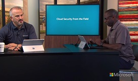 Still image from video of two people sitting at a table in front of a large display monitor talking, they both have a Surface Pro.