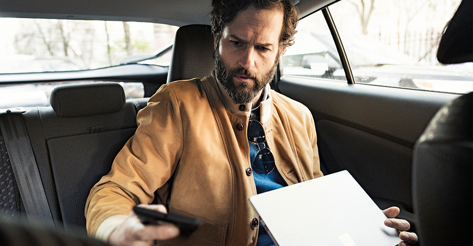 Photograph of person seated in car with laptop looking at their mobile device while touching the screen to represent multi-factor authentication