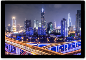 Time-lapse photograph framed in a tablet of highways crisscrossing in front of a modern cityscape at night