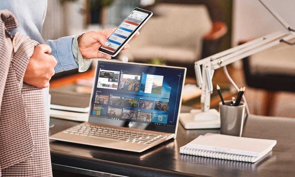 Женщина на фоне компьютера смотрит на смартфон.