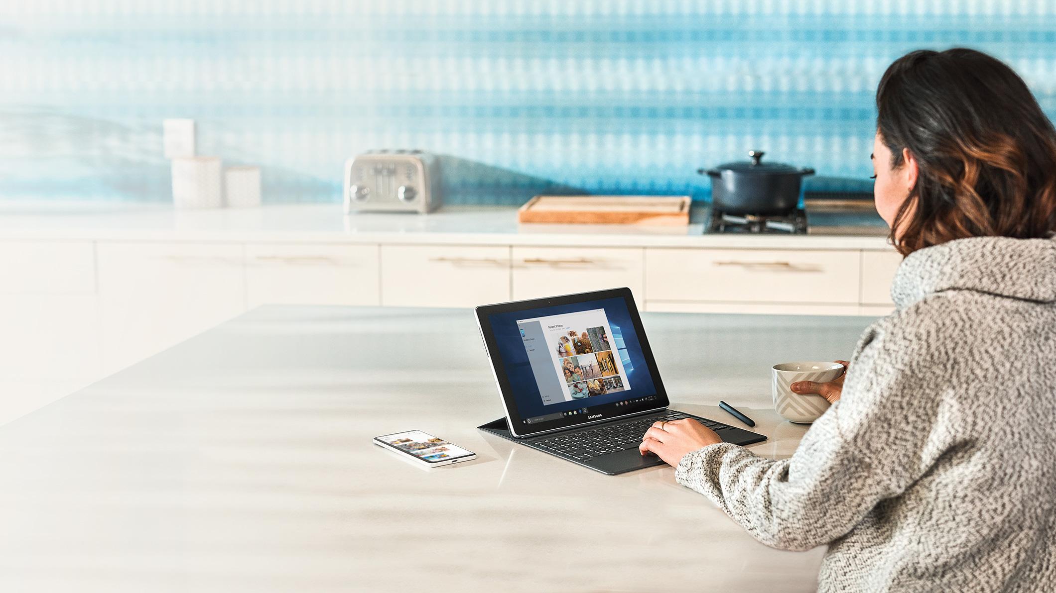 Una donna interagisce con il suo PC e il suo telefono mentre beve un caffè.