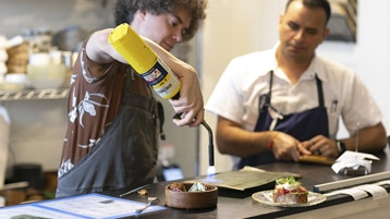 Chefs Eric Rivera and Khasbold Bataa standing at table with food, Rivera using a blowtorch