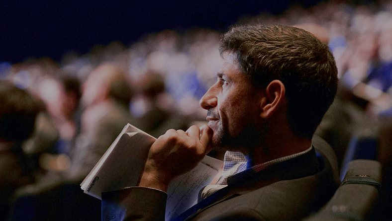 Photograph of person holding a traditional notepad seated in large audience and watching presentation.