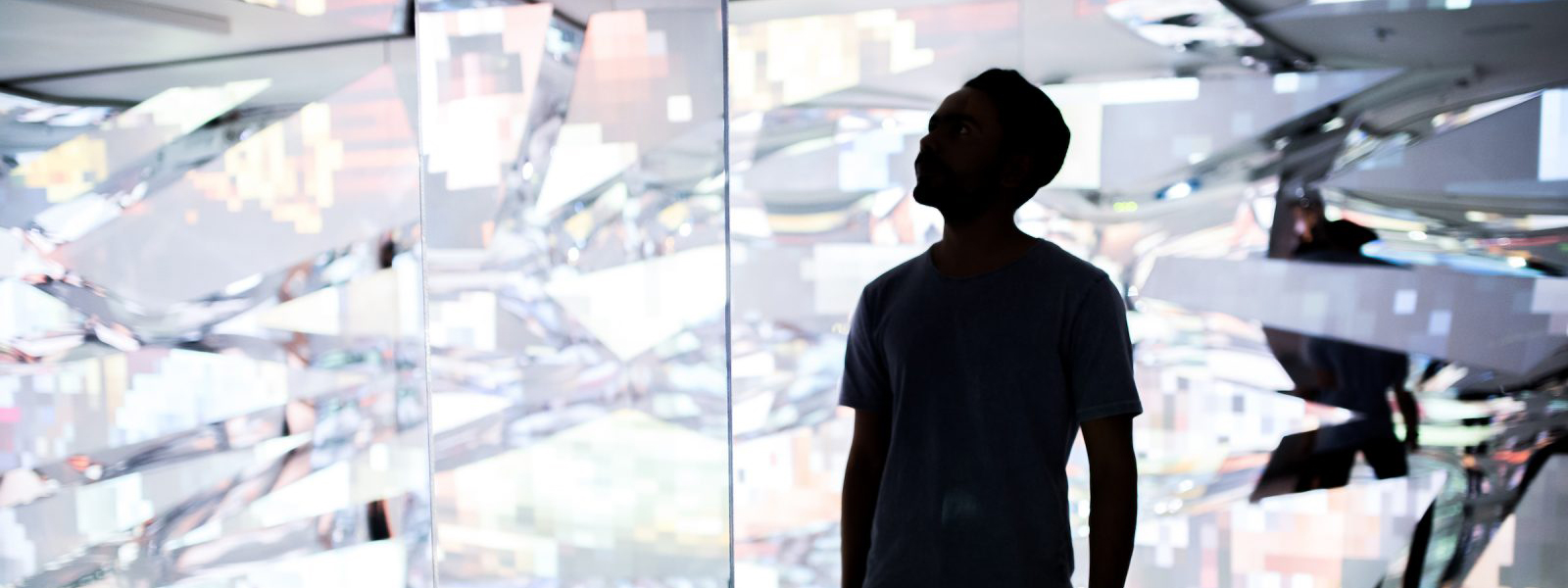 A man walks through a life-sized kaleidoscope powered by AI.