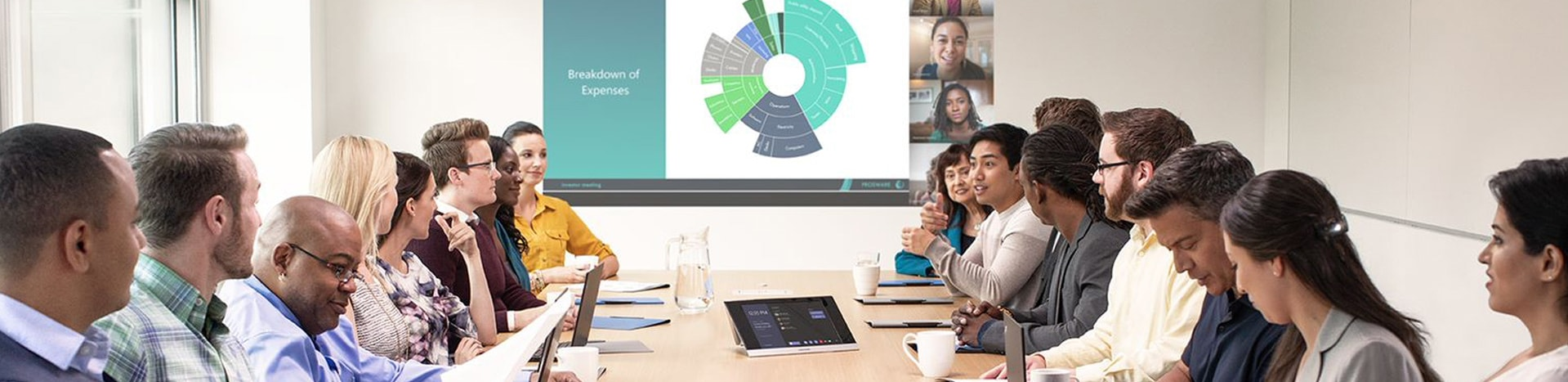 Photograph of a group of people meeting in a large conference room using a Teams device