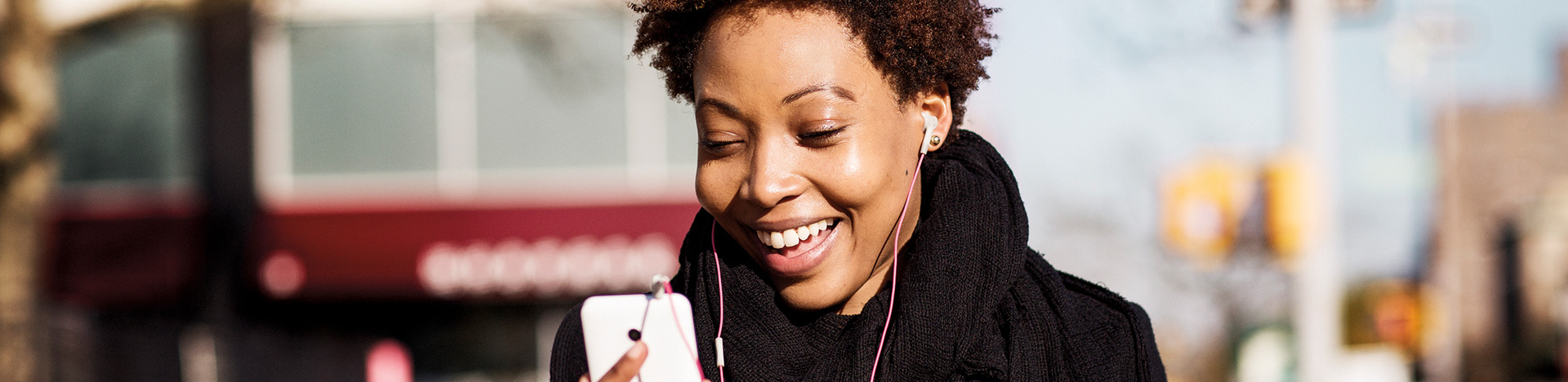 Photograph of person with headphones looking at mobile device looking at mobile phone