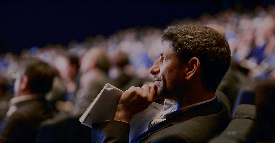 Photograph of person holding a traditional notepad seated in large audience and watching a presentation.