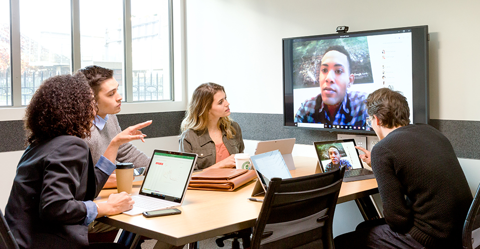 A group of co-workers video conferencing with a colleague in a conference room