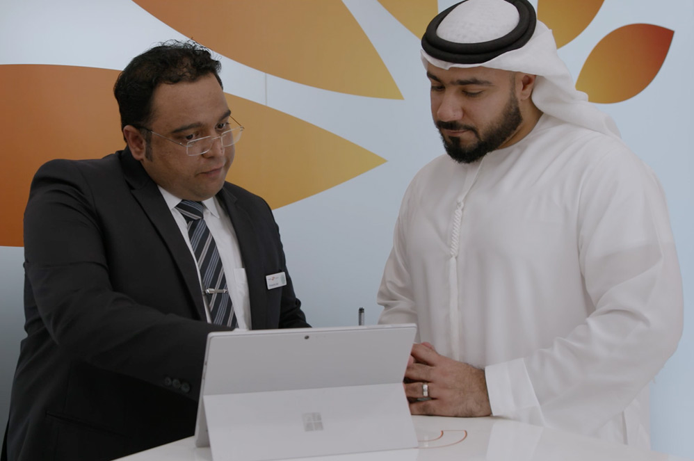 A Mashreq employee and his customer share information on a Surface Pro.
