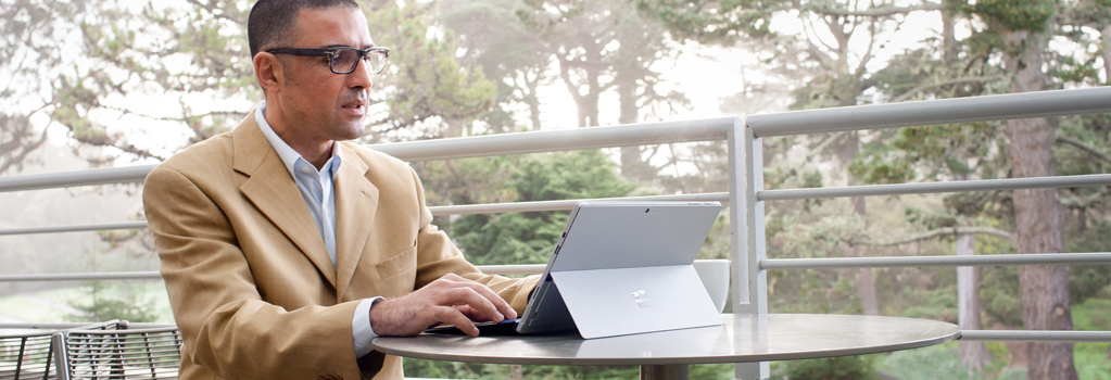 Man sitting at a table outside while working on a laptop