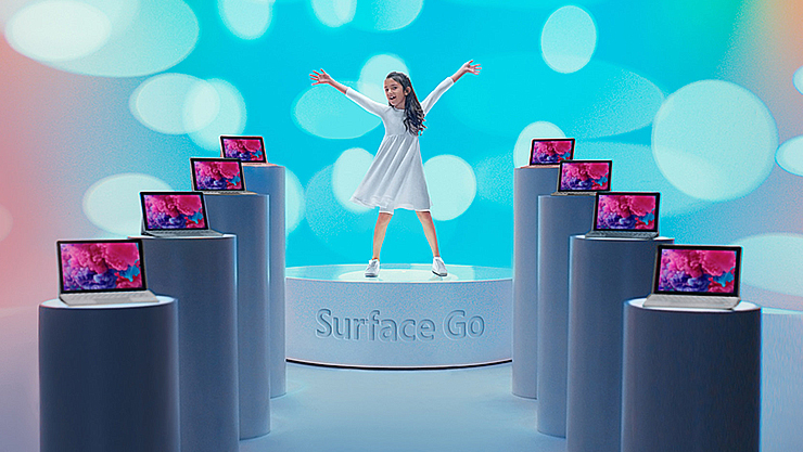 A girl celebrates, surrounded by Surface Gos