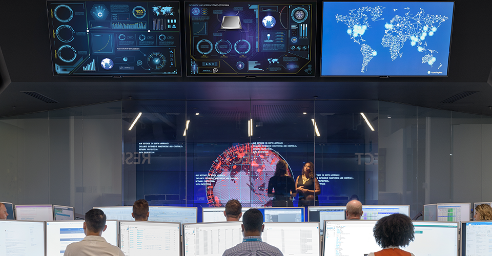 Two people in a conference room, inside an IT/Security monitoring center.