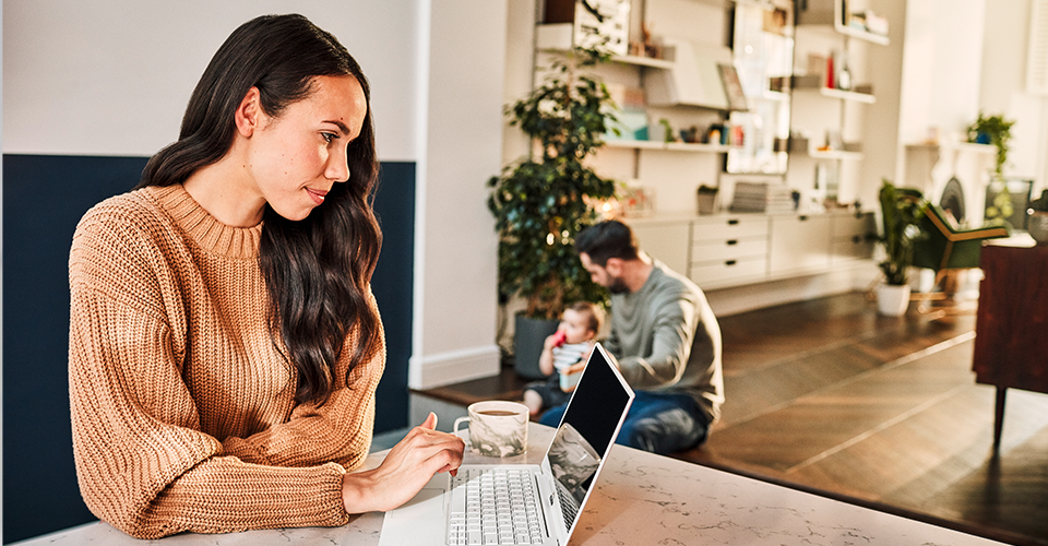 Photograph of family of three at home. One parent is sitting on floor holding young child while other parent sits at table typing on a laptop.