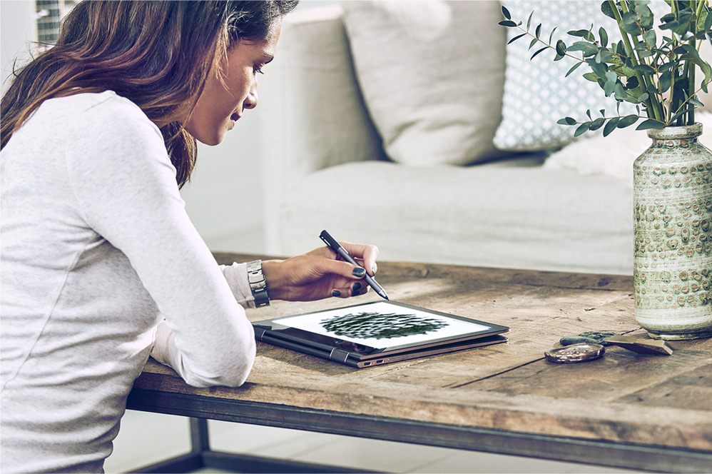 Woman using a digital pen to create an illustration on a Windows 10 computer.