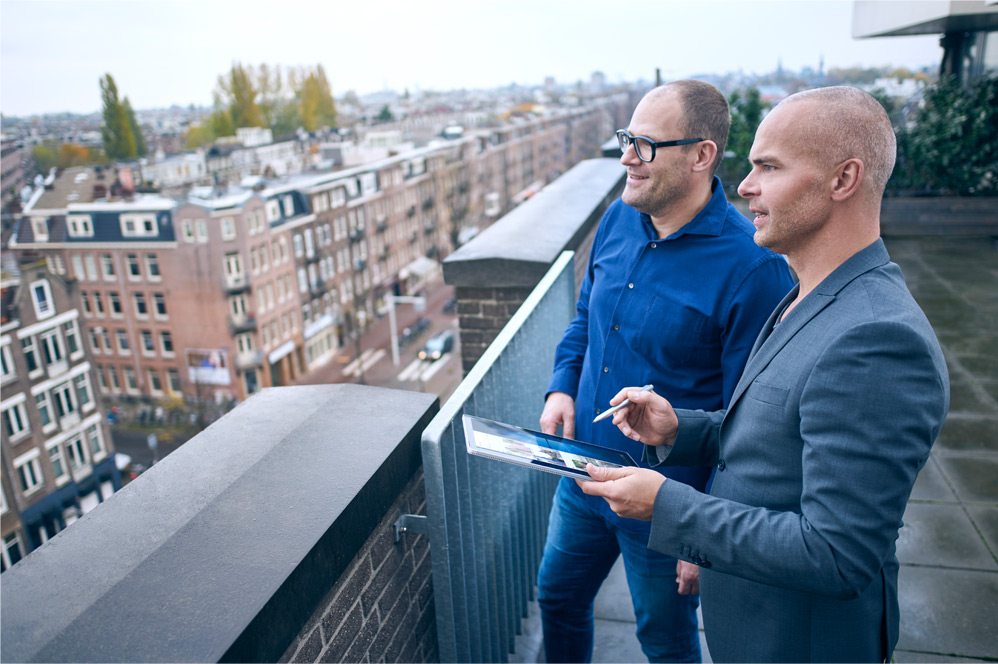 Two men on an office balcony with a Windows 10 PC.
