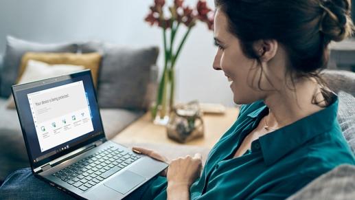 Yeni bir Windows 10 bilgisayar kullanarak masasında oturan bir kadın.