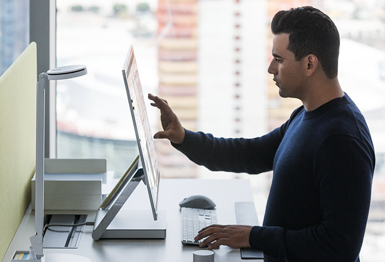 Photograph of a person standing at a desk about to touch the screen of a Surface Studio monitor