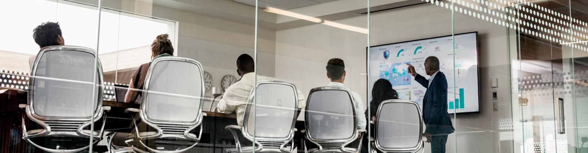 Foto einer Gruppe von Personen in einem großen modernen Konferenzraum, die an einem großen Tisch vor ihren Laptops sitzen