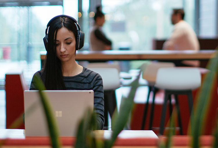 Photograph of person wearing headphones seated at a counter in a large modern building lobby working on a Surface Book