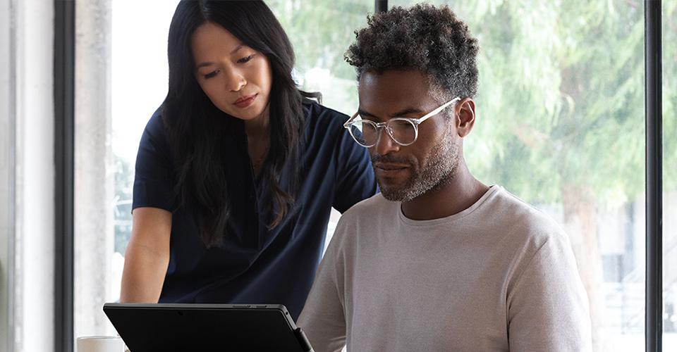 Photo de deux personnes, l'une debout et l'autre assise, consultant un Surface Book en mode ordinateur portable